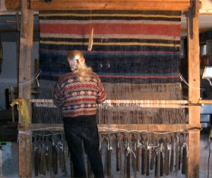 """Norman Kennedy weaving a blanket on 82""""-wide warp-weighted loom. Large wooden frame. Window weights provide tension on handspun warp."""