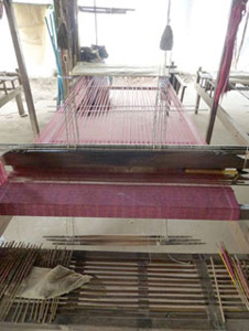 View of Khmer loom from weaver's bench. Note the three treadles are parallel to the weaver's bench.